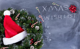 有圣诞老人盖帽和花圈的删掉的黑黑板加上文本命令 免版税库存照片
