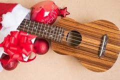 有圣诞节中看不中用的物品和礼物盒的尤克里里琴在圣诞老人帽子里面 图库摄影