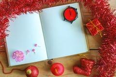 有圣诞节和新年装饰品的空白的日志在木桌,红颜色题材上的笔记本和装饰 库存图片