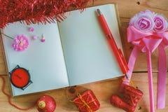 有圣诞节和新年装饰品的空白的日志在木桌,红颜色题材上的笔记本和装饰 图库摄影