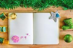 有圣诞节和新年装饰品的空白的日志在木桌,绿色题材上的笔记本和装饰 库存图片