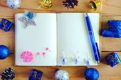 有圣诞节和新年装饰品的空白的日志在木桌,蓝色颜色题材上的笔记本和装饰 免版税库存照片
