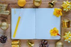 有圣诞节和新年装饰品的空白的日志在木桌,黄色颜色题材上的笔记本和装饰 库存图片