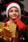 有圣诞节圣诞老人帽子的做鬼脸的孩子女孩认为ab的 库存照片