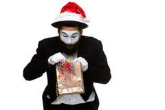 有圣诞节帽子和一件礼物的人在他们的手上 免版税库存图片