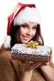 有圣诞节帽子和礼物的可爱的妇女 图库摄影