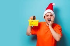 有圣诞节帽子和超级市场篮子的人 免版税图库摄影