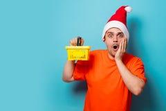 有圣诞节帽子和超级市场篮子的人 库存图片