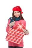 有圣诞节帽子拉扯礼物盒的亚裔女孩从购物袋 库存照片