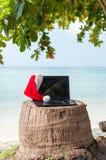有圣诞节帽子的一台膝上型计算机在海滩 免版税图库摄影