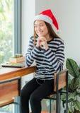 有圣诞节帽子的亚裔十几岁的女孩和微笑面对休息她 免版税库存照片