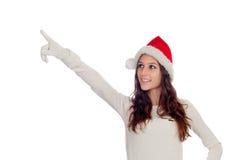 有圣诞节帽子的可爱的偶然女孩指向某事的 库存图片