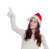 有圣诞节帽子的可爱的偶然女孩指向某事的 免版税图库摄影