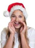 有圣诞节帽子的呼喊的妇女 免版税库存照片