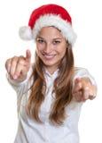 有圣诞节帽子的笑的妇女指向与两个手指的照相机的 库存照片