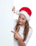 有圣诞节帽子的美丽的妇女指向在牌的 图库摄影