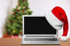 有圣诞节帽子的膝上型计算机 免版税库存图片