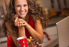 有圣诞节快餐的愉快的主妇使用膝上型计算机在厨房里 免版税库存照片