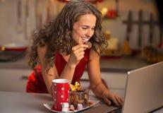 有圣诞节快餐的主妇使用膝上型计算机 免版税库存图片