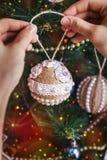 有圣诞节手工制造麻线玩具的手 免版税库存图片