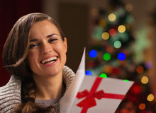 有圣诞节明信片的愉快的少妇 库存图片