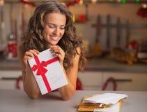 有圣诞节明信片的愉快的年轻主妇在厨房里 库存图片