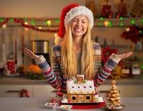 有圣诞节曲奇饼房子的少年女孩 库存照片