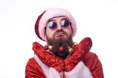 有圣诞节玩具的一个人在胡子和在圣诞老人项目衣服握他的手在他的头下并且扭动他的面孔 免版税库存照片