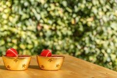 有圣诞节球的两个碗在一张木桌上 免版税库存照片