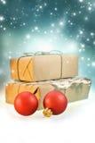 有圣诞节球的手工制造礼物盒在发光的背景 库存照片