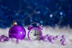 有圣诞节球的紫色小的在蓝色bokeh的时钟和小珠 免版税库存图片