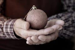 有圣诞节球的老人在他的手上 免版税图库摄影