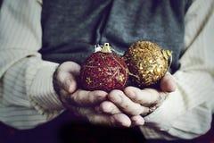 有圣诞节球的老人在他的手上 免版税库存照片
