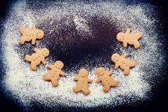 有圣诞节的姜饼人在黑暗的表上的舞蹈 免版税库存照片