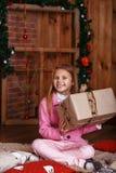 有圣诞节礼品的愉快的小女孩 库存照片