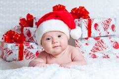 有圣诞节礼品的新出生的男婴圣诞老人 图库摄影