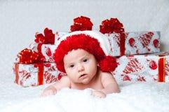 有圣诞节礼品的新出生的男婴圣诞老人 库存照片