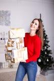 有圣诞节礼物和圣诞树的微笑的少妇 免版税库存照片