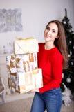 有圣诞节礼物和圣诞树的微笑的少妇 图库摄影