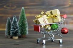 有圣诞节礼物和圣诞节装饰的购物车 库存图片