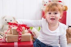 有圣诞节礼物和玩具熊的女孩在背景中 免版税库存照片