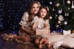 有圣诞节礼物的两个女孩在家 免版税库存照片