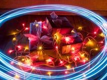 有圣诞节礼物的从绘画的箱子与有灯的诗歌选和踪影由蓝色光 免版税图库摄影