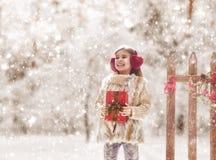 有圣诞节礼物的女孩在冬天步行 免版税库存照片