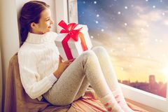 有圣诞节礼物的女孩在窗口基石在冬天 图库摄影