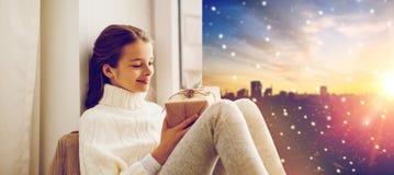 有圣诞节礼物的女孩在窗口基石在冬天 免版税库存图片