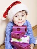 有圣诞节礼物的小逗人喜爱的男孩在家 关闭在箱子的情感面孔在圣诞老人红色帽子,生活方式人 库存图片