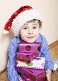 有圣诞节礼物的小逗人喜爱的男孩在家 关闭在箱子的情感面孔在圣诞老人红色帽子 免版税库存图片