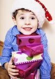 有圣诞节礼物的小逗人喜爱的男孩在家 关闭情感 库存图片