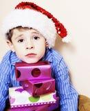 有圣诞节礼物的小逗人喜爱的男孩在家 关闭情感 图库摄影